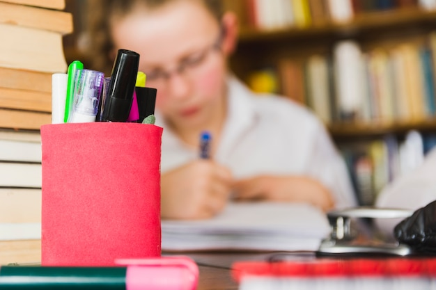 Meisje dat bij bureau met kantoorbehoeften bestudeert