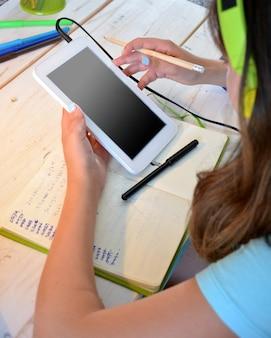 Meisje dat bij haar bureau bestudeert dat een tablet gebruikt