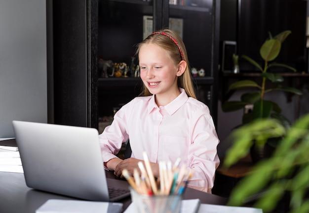 Meisje dat bij haar collega's van huis glimlacht