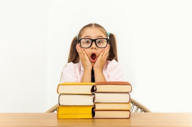 Meisje dat bij lijst aangaande witte achtergrond bestudeert