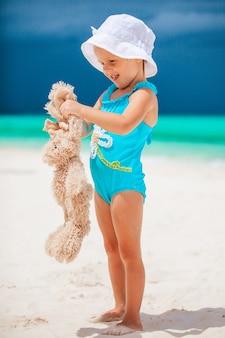Meisje dat bij tropisch wit strand zandkasteel maakt