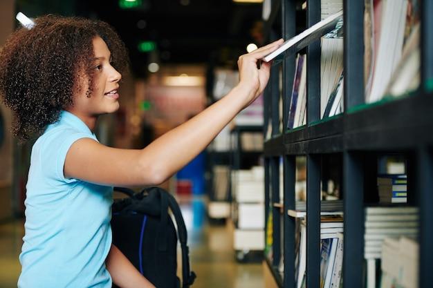 Meisje dat boek in boekhandel neemt