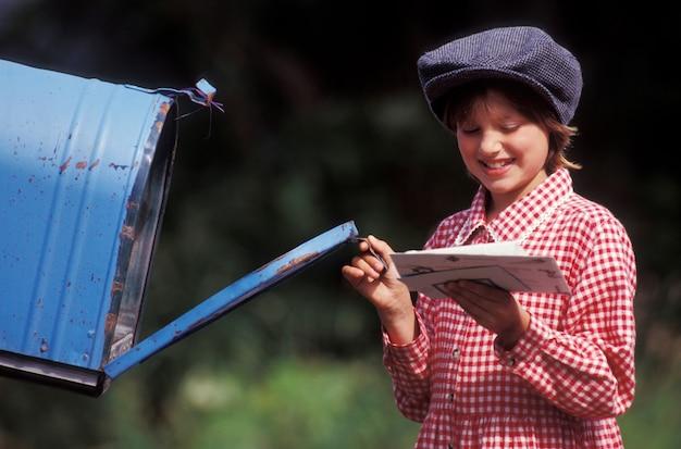 Meisje dat brieven van brievenbus haalt