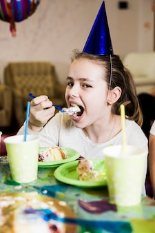 Meisje dat cake op verjaardagspartij eet