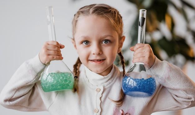 Meisje dat chemische elementen in ontvangers houdt
