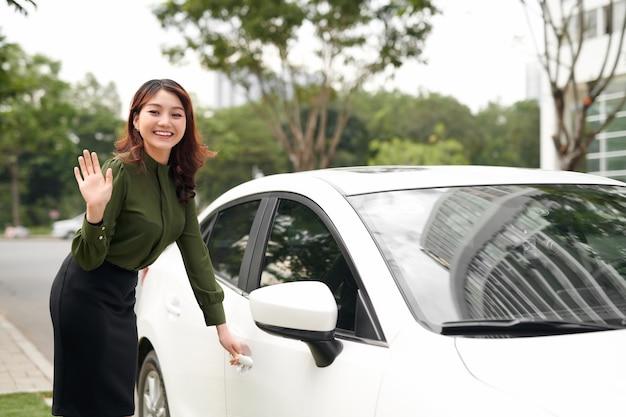 Meisje dat de auto ingaat op weg naar de stedelijke levensstijl van de weg, glimlachend en zwaaiend om weg te gaan