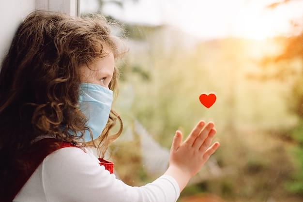 Meisje dat de blauwe medische zitting van het gezichtsmasker op vensterbank met weinig rood hart op venster draagt als manier om dankbaarheid te tonen aan artsen en verpleegsters voor hulp in de strijd tegen de ziekte. covid-19