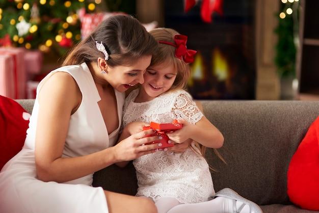 Meisje dat de doos van de gift van kerstmis met mummie uitpakt