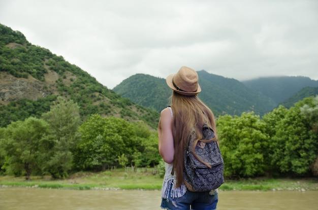 Meisje dat de groene bergen en de rivier bewondert