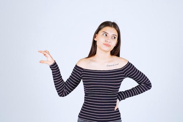 Meisje dat de hoeveelheid of maatregelen van een product toont.