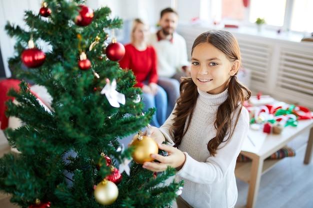 Meisje dat de kerstboom verfraait
