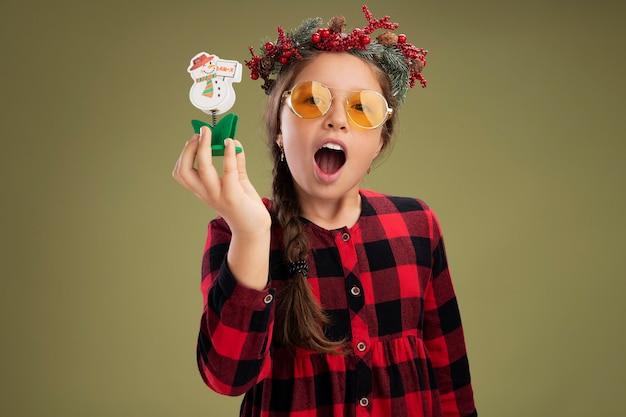 Meisje dat de kroon van kerstmis in gecontroleerde kleding draagt die kerstmisstuk speelgoed houdt die camera gelukkig en opgewekt status over groene achtergrond bekijken