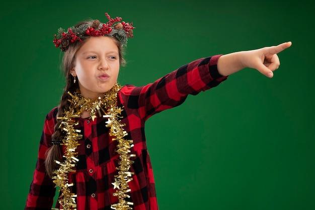 Meisje dat de kroon van kerstmis in gecontroleerde kleding met klatergoud om hals draagt die met ernstig gezicht opzij kijkt dat met wijsvinger naar iets richt