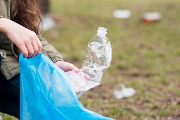 Meisje dat de plastic fles van grond schoonmaakt