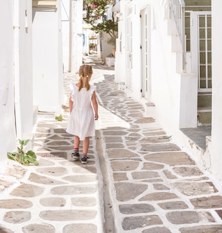 Meisje dat de smalle steeg in griekenland loopt