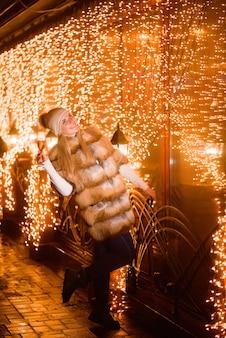Meisje dat de winterhoed met glas champagne draagt bij partij over vakantie gloeiend goud