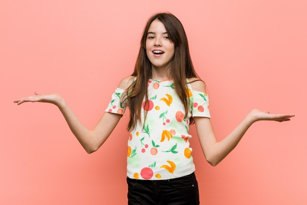 Meisje dat de zomerkleren draagt tegen een rode muur die verward en twijfelachtig schouders ophaalt om een exemplaarruimte vast te houden.