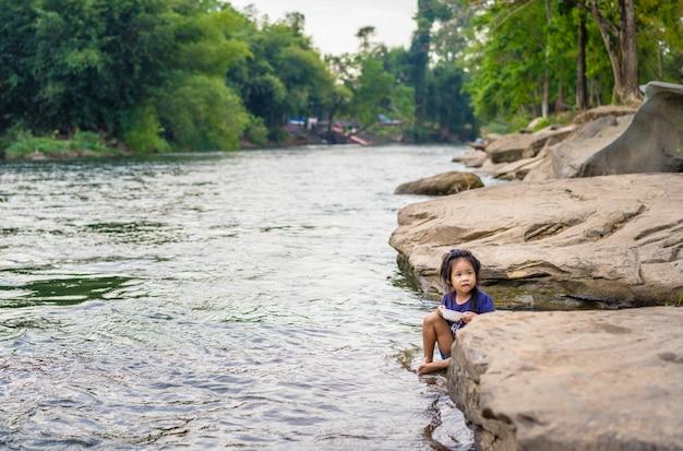 Meisje dat dichtbij de rivier eet