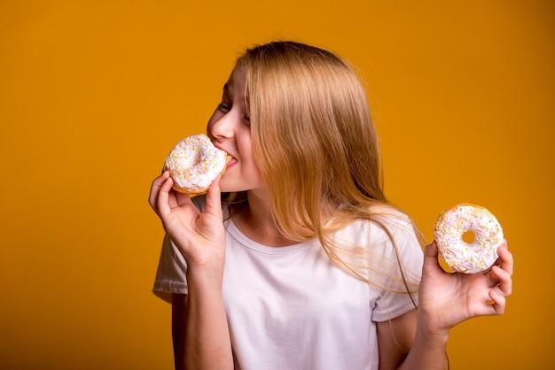 Meisje dat donuts op een gele achtergrond eet