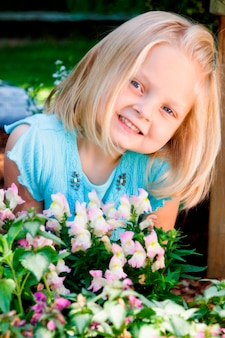 Meisje dat door bloemen, portret glimlacht