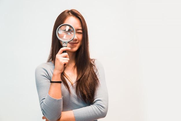 Meisje dat door een vergrootglas kijkt