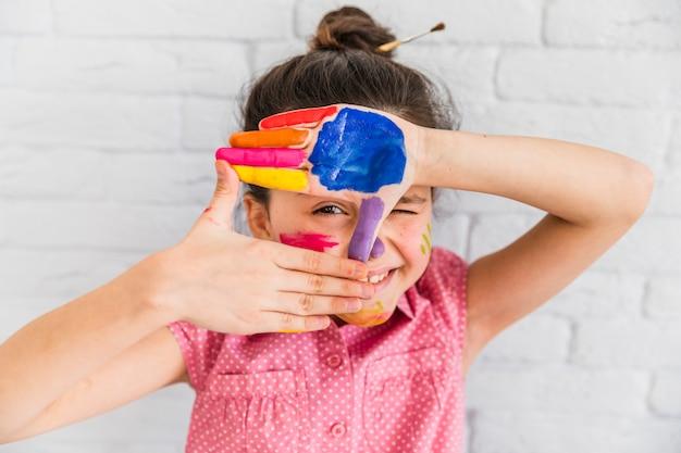 Meisje dat door vingerkader kijkt met verven op palm tegen witte bakstenen muur