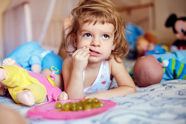 Meisje dat druiven op bed eet