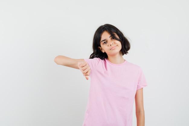 Meisje dat duim in roze t-shirt toont en zelfverzekerd, vooraanzicht kijkt.