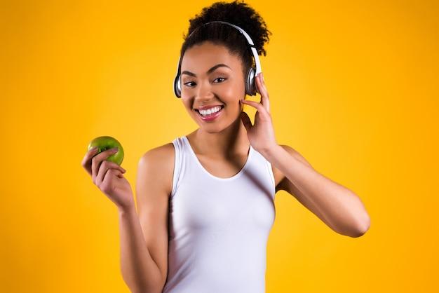 Meisje dat een appel in haar hand houdt en aan muziek luistert