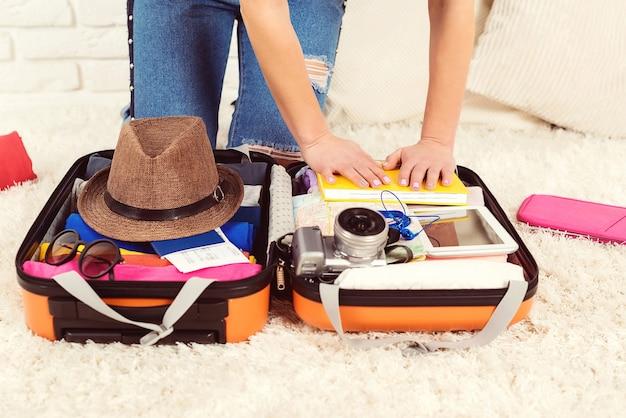Meisje dat een bagage inpakt voor een nieuwe reis.