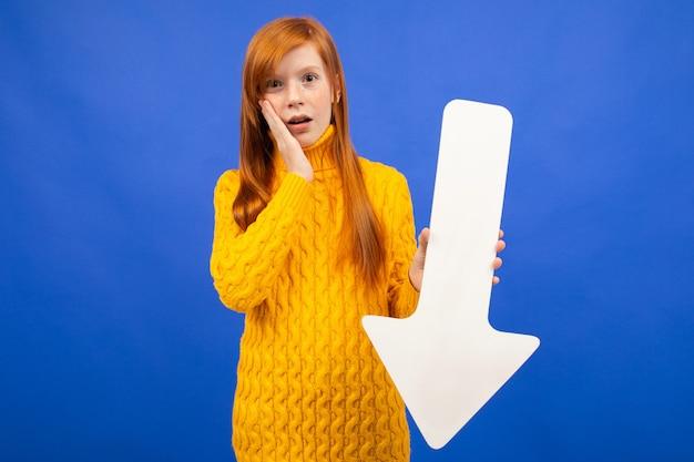 Meisje dat een benedenpijl uit document op blauw houdt