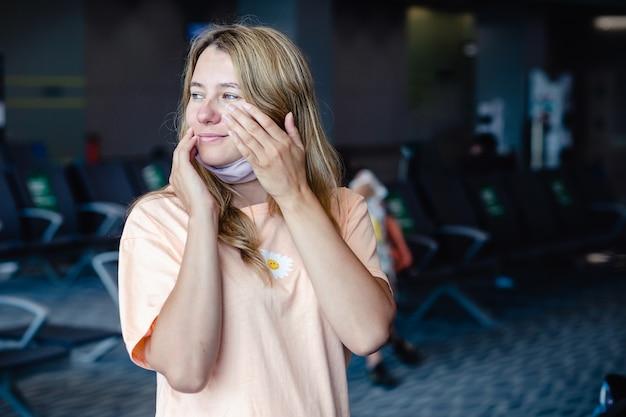 Meisje dat een beschermingsmasker draagt voor coronavirus of covid 19 die haar gezicht met vuile handen in luchthaven wrijft.
