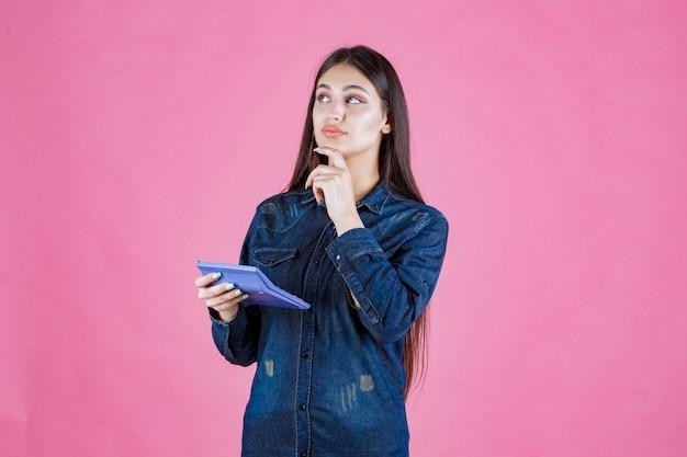 Meisje dat een blauwe calculator houdt en denkt