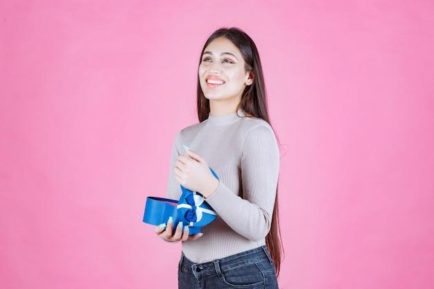 Meisje dat een blauwe giftdoos houdt en glimlacht