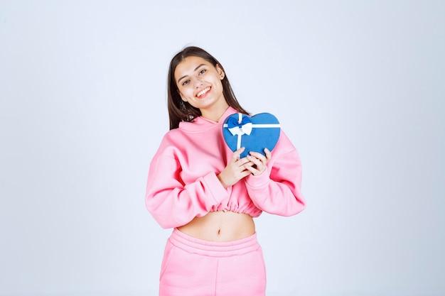 Meisje dat een blauwe giftdoos van de hartvorm houdt en het demonstreert.