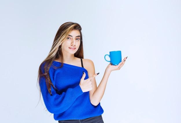 Meisje dat een blauwe koffiekop houdt en iemand toont.