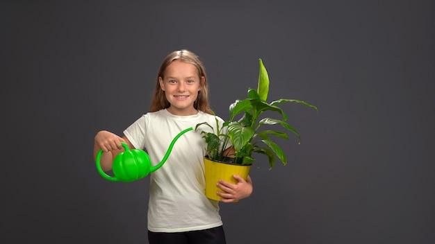 Meisje dat een bloem in een pot water geeft met behulp van een grappige gieter die alles in haar handen houdt