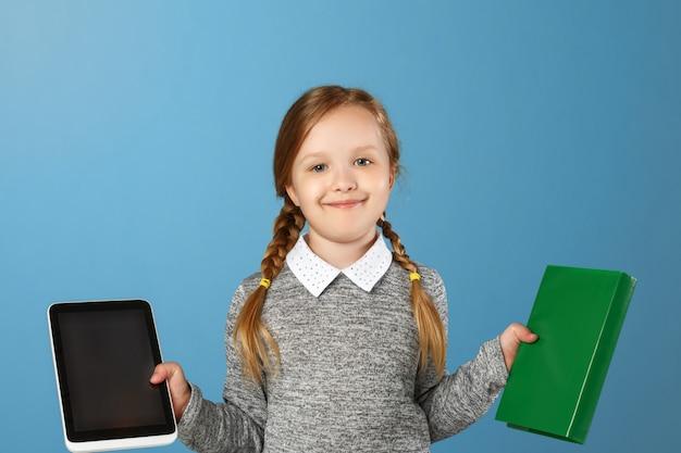 Meisje dat een boek en een tablet houdt.