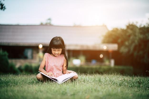 Meisje dat een boek in de huistuin leest
