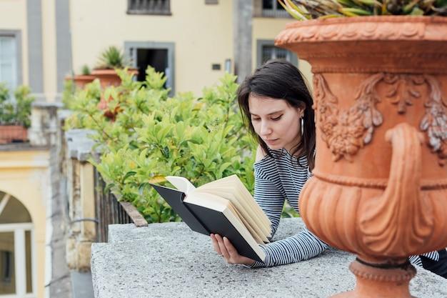 Meisje dat een boek in de straat leest