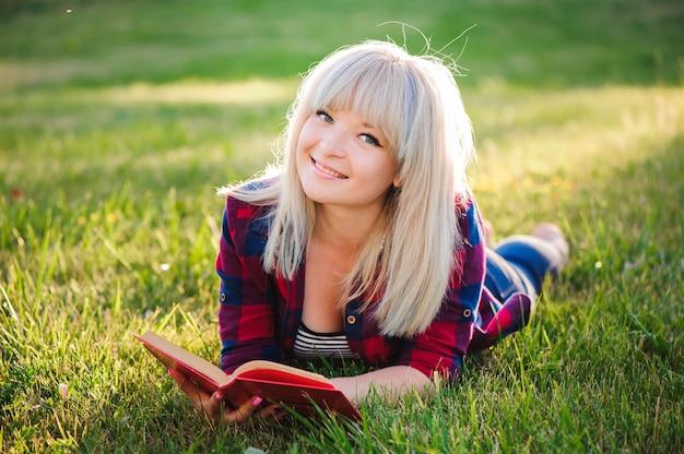 Meisje dat een boek in een de zomerpark leest