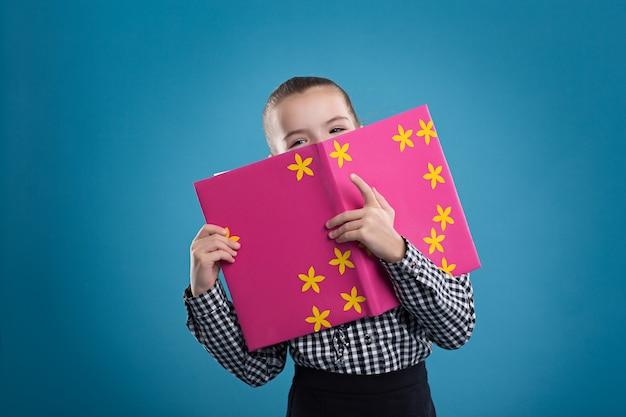 Meisje dat een boek in een roze dekking leest