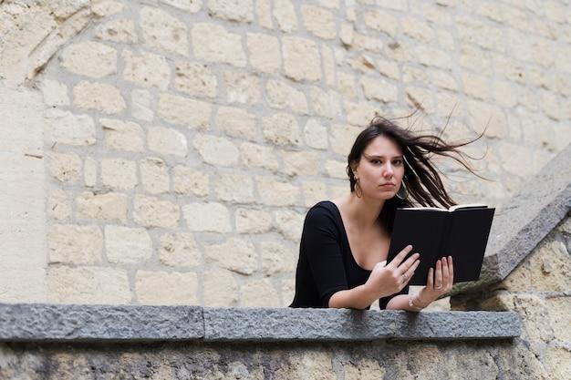 Meisje dat een boek in een winderige dag leest
