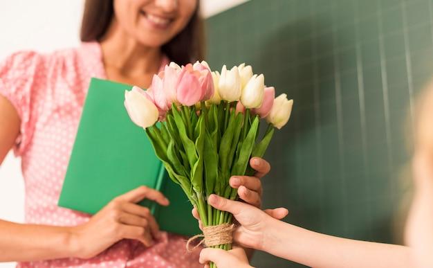 Meisje dat een boeket bloemen overhandigt aan haar leraar