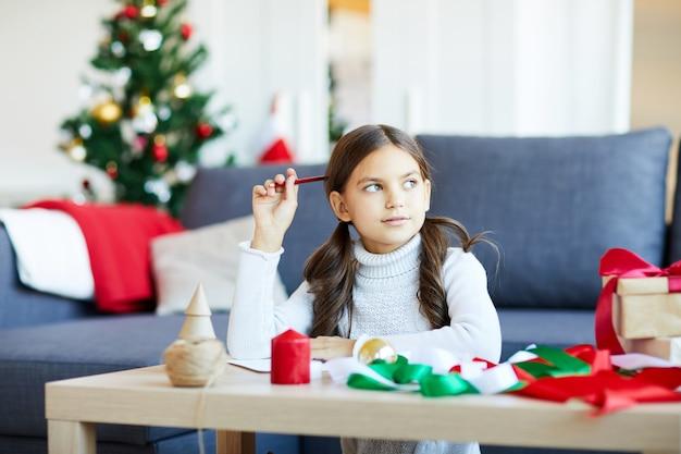 Meisje dat een brief schrijft voor de kerstman
