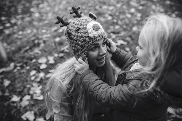 Meisje dat een cap op haar moeder