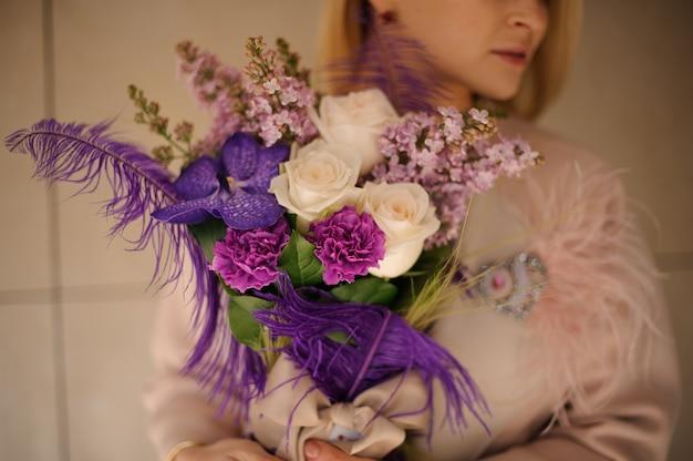 Meisje dat een de lenteboeket van tedere roze en violette bloemen houdt