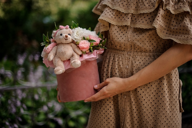 Meisje dat een doos houdt die met bloemen wordt gevuld