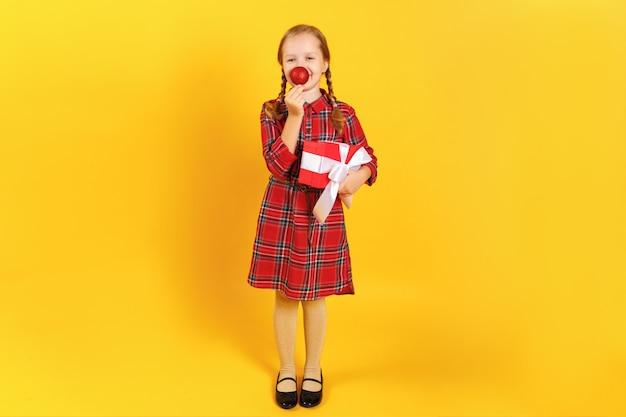 Meisje dat een doos met een gift houdt en de neus van een bal van kerstmis maakt.