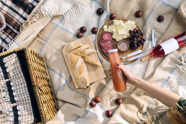 Meisje dat een fles sap houdt. lunch met salamikaas en stokbrood in het park op een sprei. bovenaanzicht